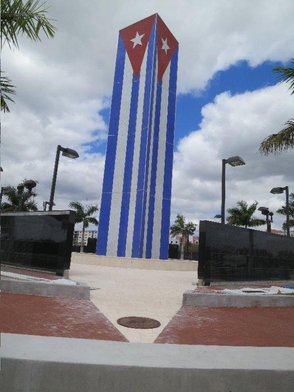 Aqui vemos las pardedes con los martires y victimas, la bandera cubana y un medallón