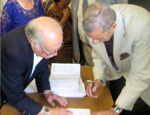 El momento en que el miembro de la Comisión Electoral Roosvelt F. Bernal le presentaba para su firma al nuevo Decano Salvador Romani el acta de votación